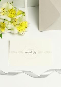 Grußpostkarte auf weißem hintergrund, blumenstrauß blüht, graues band