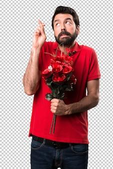Gut aussehender mann, der blumen mit seiner fingerkreuzung hält