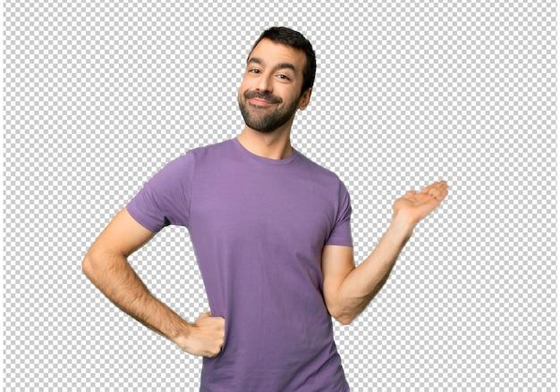 Gut aussehender mann, der copyspace imaginär auf der palme hält, um eine anzeige einzufügen