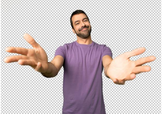 Gut aussehender mann, der darstellt und einlädt, um mit der hand zu kommen