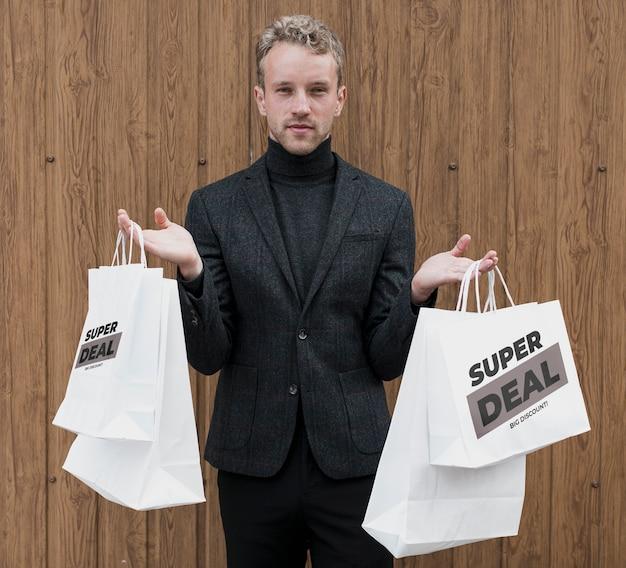 Gut aussehender mann, der einkaufstaschen hält