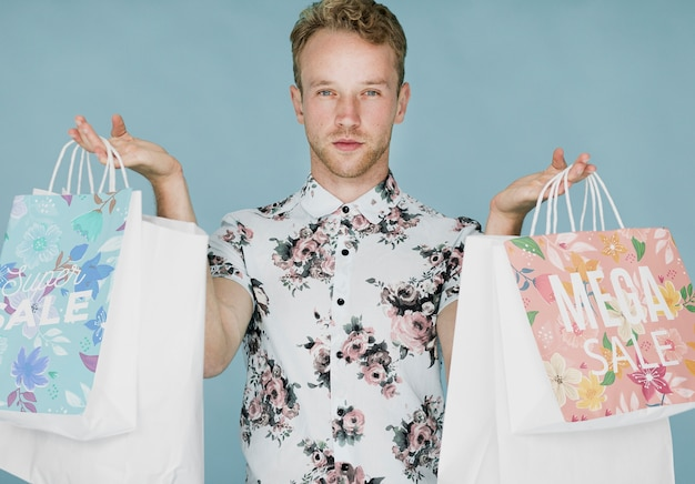 Gut aussehender mann, der mehrfache einkaufstaschen hält