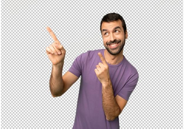 Gut aussehender mann, der mit dem zeigefinger zeigt und oben schaut