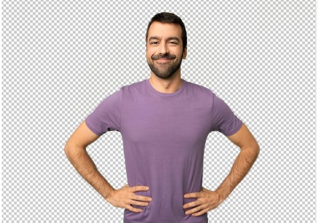 Gut aussehender mann, der mit den armen an der hüfte aufwirft und zur vorderseite schauen lacht