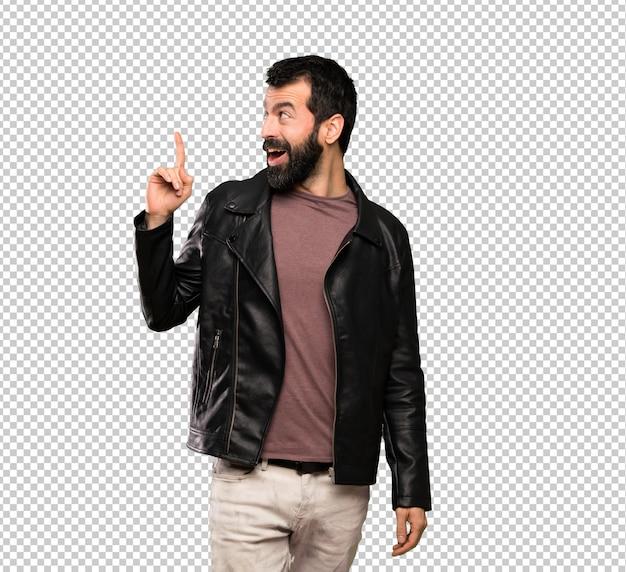 Gut aussehender mann mit bart, der beabsichtigt, die lösung beim anheben eines fingers zu verwirklichen