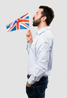 Gut aussehender mann mit bart, der eine flagge des vereinigten königreichs hält