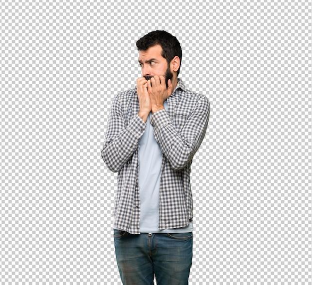 Gut aussehender mann mit bart nervös und erschrocken, die hände zum mund setzend