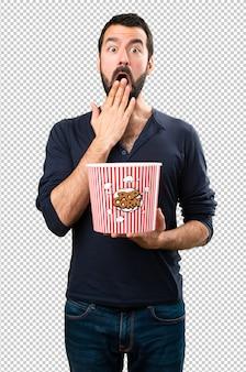 Gut aussehender mann mit bart popcorn essend
