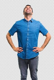 Gut aussehender mann mit blauem hemdstand und oben schauen