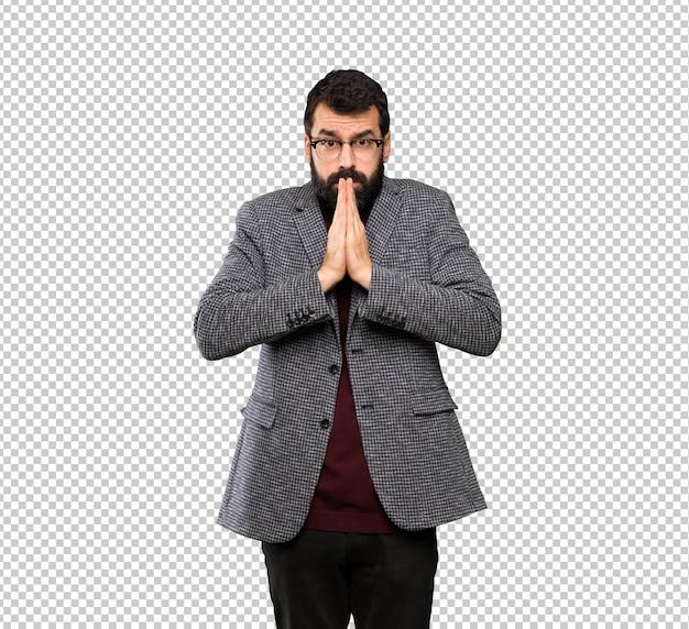 Gut aussehender mann mit brille hält handfläche zusammen. person bittet um etwas