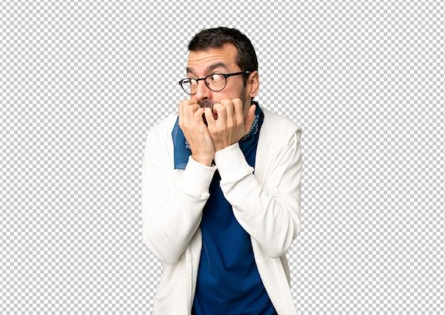 Gut aussehender mann mit brille ist ein bisschen nervös und verängstigt, die hände in den mund zu setzen