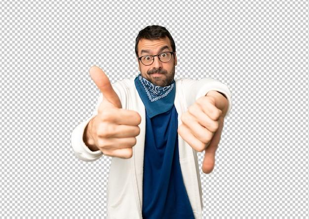 Gut aussehender mann mit brille machen gut-schlechtes zeichen. unbestimmt zwischen ja oder nein
