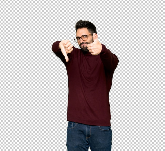 Gut aussehender mann mit brille machen gut-schlechtes zeichen. unentschieden zwischen ja oder nein