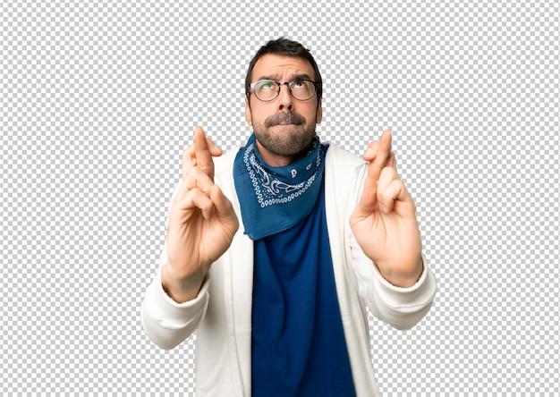Gut aussehender mann mit brille mit den fingern, die das beste kreuzen und wünschen