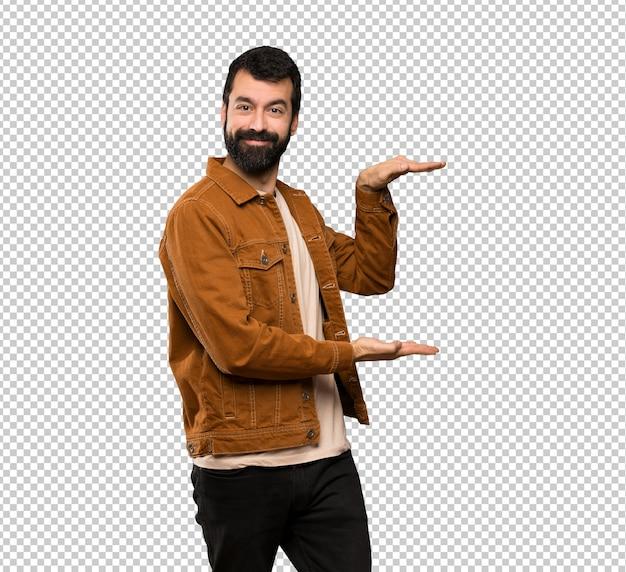 Gut aussehender mann mit dem bart, der copyspace hält, um eine anzeige einzufügen