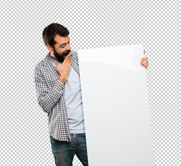 Gut aussehender mann mit dem bart, der ein leeres plakat hält
