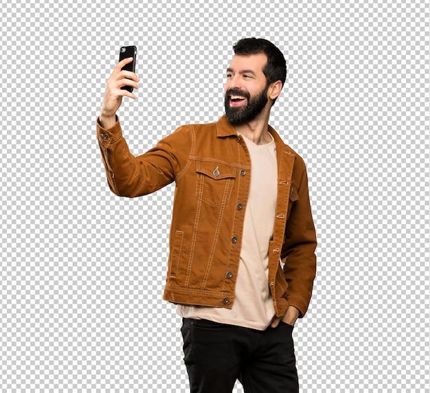 Gut aussehender mann mit dem bart, der ein selfie macht