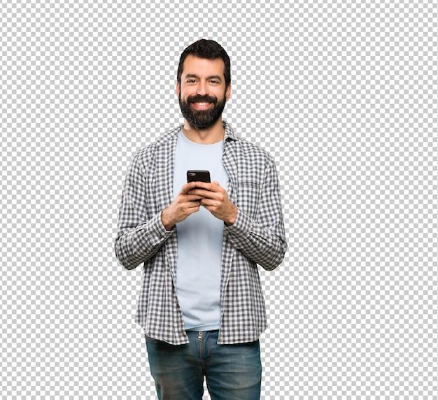 Gut aussehender mann mit dem bart, der eine mitteilung mit dem mobile sendet