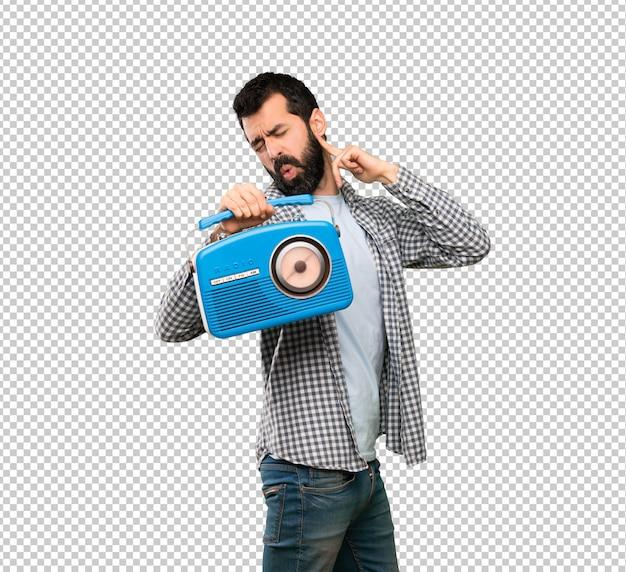 Gut aussehender mann mit dem bart, der einen radio hält