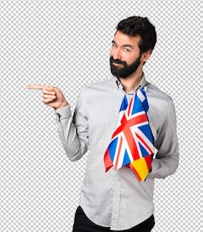 Gut aussehender mann mit dem bart, der viele flaggen hält und auf den seitenstreifen zeigt