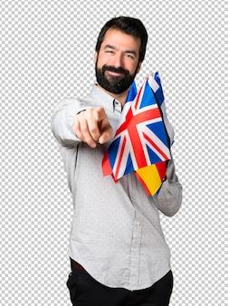 Gut aussehender mann mit dem bart, der viele flaggen hält und auf die front zeigt