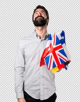 Gut aussehender mann mit dem bart, der viele flaggen hält und oben schaut
