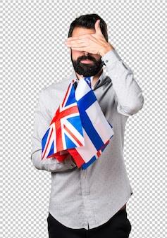 Gut aussehender mann mit dem bart, der viele flaggen hält und seine augen bedeckt