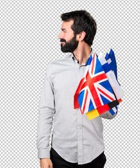 Gut aussehender mann mit dem bart, der viele flaggen hält und seitlich schaut