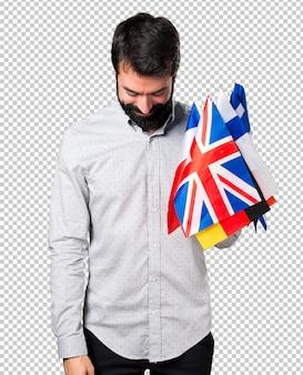 Gut aussehender mann mit dem bart, der viele flaggen hält und unten schaut
