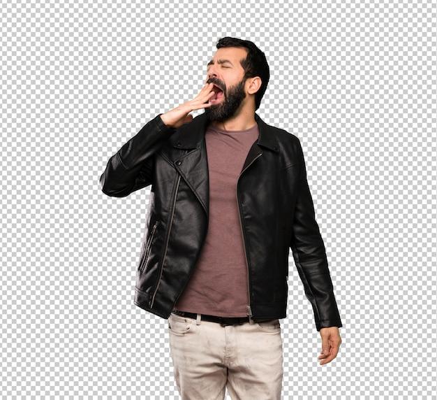 Gut aussehender mann mit dem bart, der weit offenem mund mit der hand gähnt und bedeckt