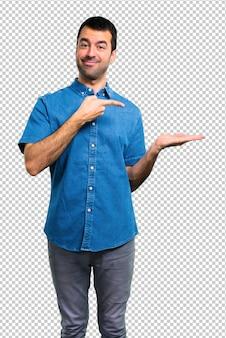 Gut aussehender mann mit dem blauen hemd, das copyspace eingebildet auf der palme hält