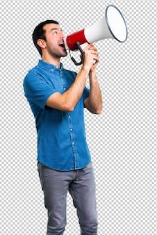 Gut aussehender mann mit dem blauen hemd, das ein megaphon hält