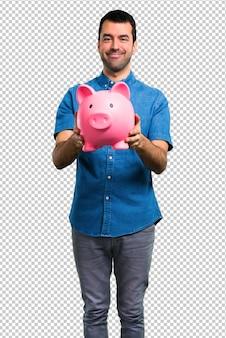 Gut aussehender mann mit dem blauen hemd, das ein piggybank hält