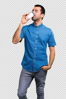 Gut aussehender mann mit dem blauen hemd, das kaffee zum mitnehmen hält