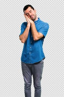 Gut aussehender mann mit dem blauen hemd, das schlafgeste macht