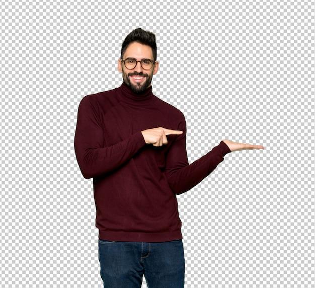 Gut aussehender mann mit den gläsern, die copyspace eingebildet auf der palme halten, um eine anzeige einzufügen