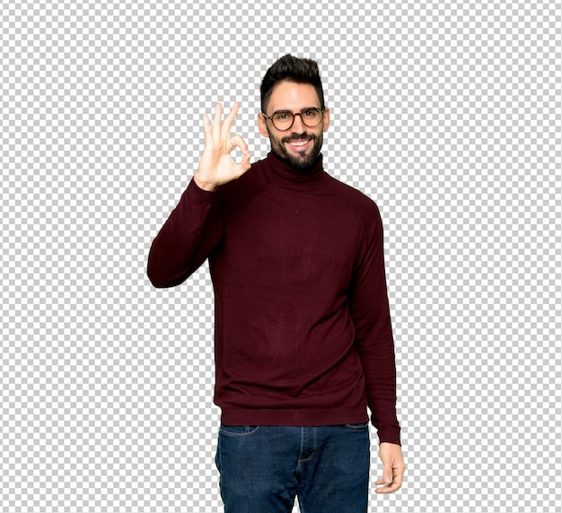 Gut aussehender mann mit den gläsern, die ein okayzeichen mit den fingern zeigen