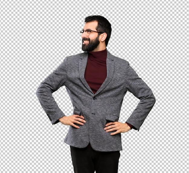 Gut aussehender mann mit den gläsern, die mit den armen an der hüfte und am lächeln aufwerfen