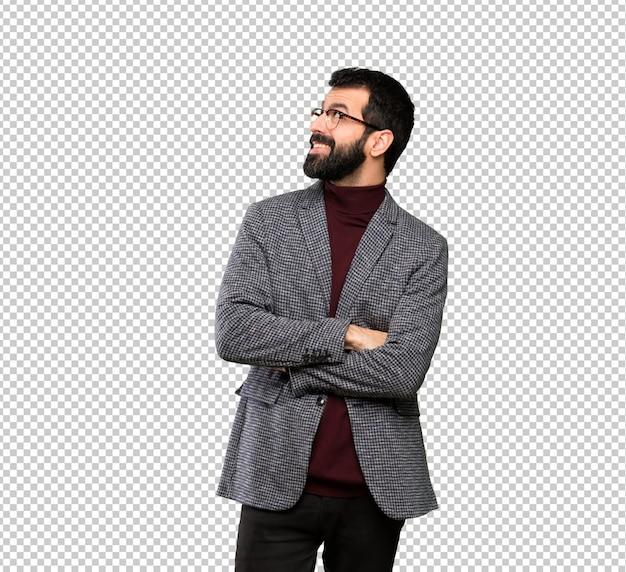 Gut aussehender mann mit den gläsern, die oben beim lächeln schauen