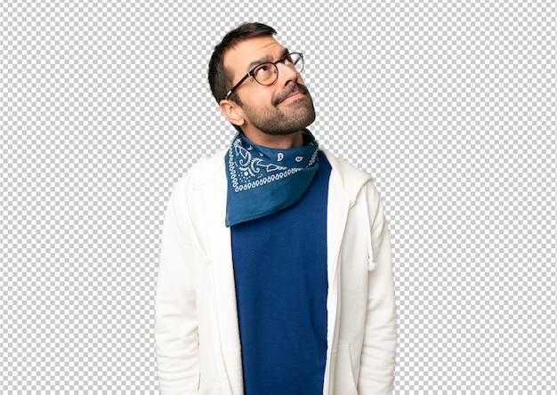 Gut aussehender mann mit den gläsern, die oben mit ernstem gesicht schauen