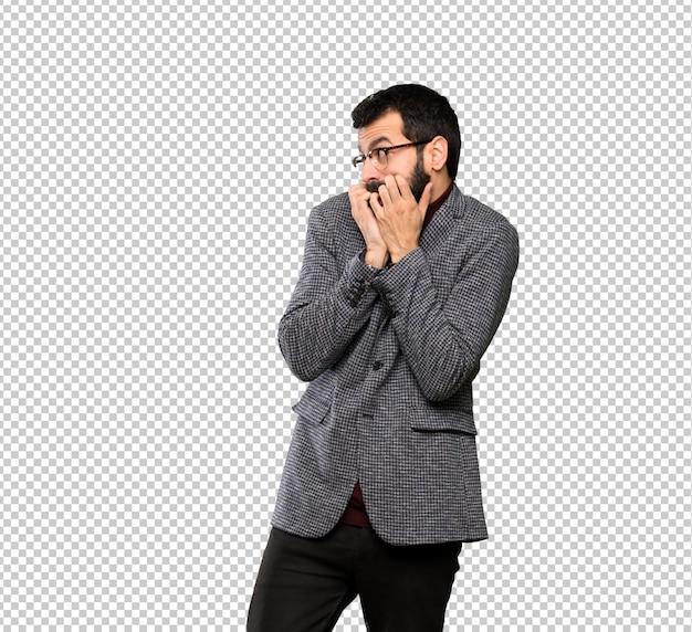 Gut aussehender mann mit den gläsern nervös und erschrocken, hände zum mund setzend