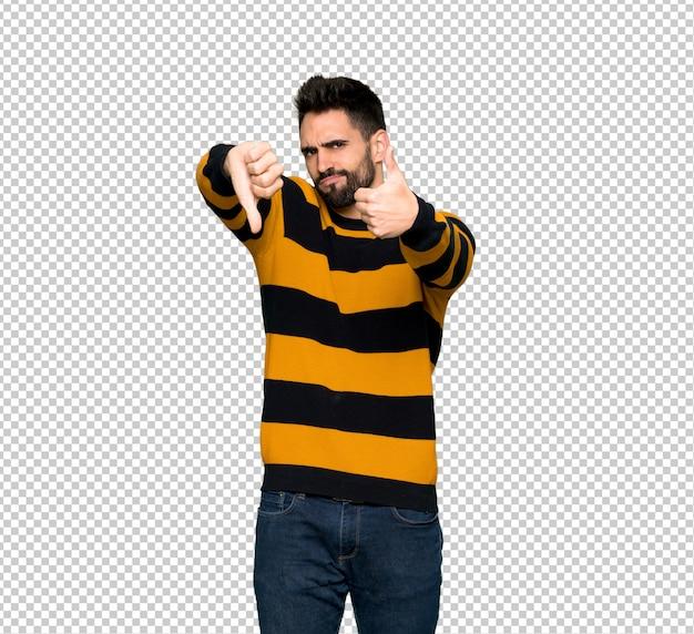 Gut aussehender mann mit der gestreiften strickjacke, die gut-schlechtes zeichen macht. unentschieden zwischen ja oder nein