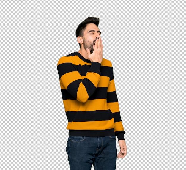 Gut aussehender mann mit der gestreiften strickjacke, die weit offenen mund mit der hand gähnt und bedeckt