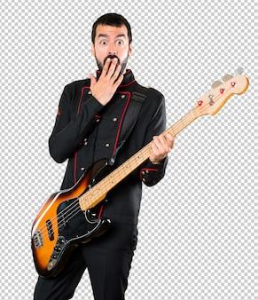 Gut aussehender mann mit der gitarre, die überraschungsgeste macht