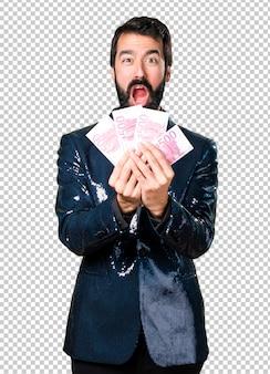Gut aussehender mann mit der paillettejacke, die viel geld nimmt