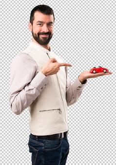 Gut aussehender mann mit der weste, die ein kleines auto hält