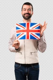 Gut aussehender mann mit der weste, die eine flagge des vereinigten königreichs hält