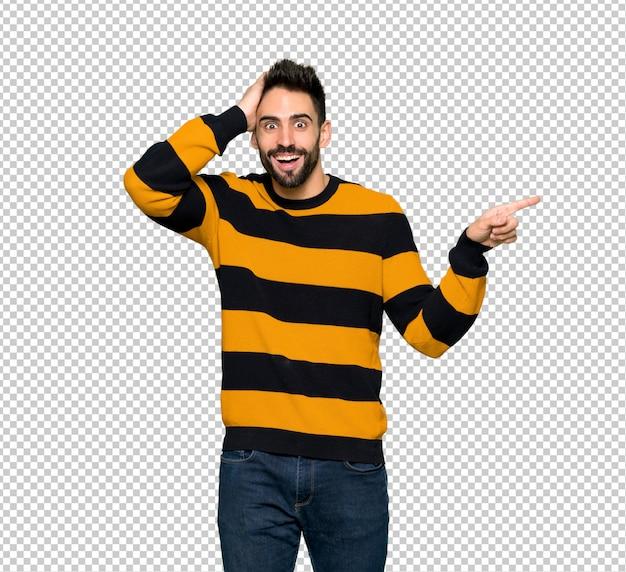 Gut aussehender mann mit gestreifter strickjacke finger auf die seite zeigend und ein produkt darstellend