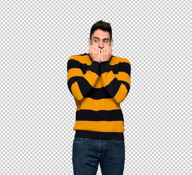 Gut aussehender mann mit gestreifter strickjacke ist ein bisschen nervös und erschrocken, die hände in den mund zu setzen