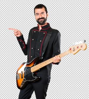 Gut aussehender mann mit gitarre zeigend auf das seitliche